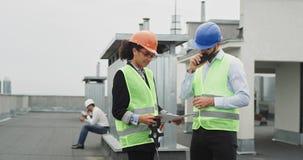 In een moderne bouwwerf op de ingenieur van de dak mooie Afrikaanse dame met de architect die het plan analyseren van stock footage