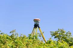 Een moderne geodetische ontvanger werkt autonoom op het gebied onder wild frambozenstruikgewas royalty-vrije stock afbeeldingen