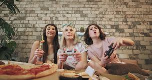 In een moderne slaapkamer met een mooi ontwerp drie vriendendames die in PlayStation spelen en pizza zeer eten stock video