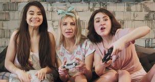 In een moderne slaapkamergroep vrienden jonge dames die op een PlayStation-videospelletje voor de camera zeer spelen stock videobeelden