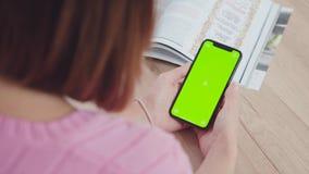 Een moderne smartphone in de handen van een jonge vrouw, het groene scherm stock video