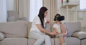 In een moderne woonkamer op de bank een rijpe moeder met haar dochter die een tijd doorbrengt die samen een virtuele werkelijkhei stock footage
