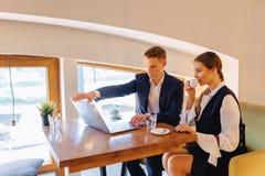Een modieus paar drinkt ochtendkoffie bij de koffie en de werken met laptop, jonge zakenlieden en een freelancers stock fotografie
