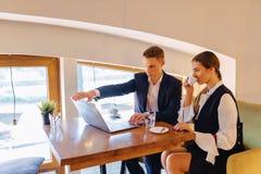Een modieus paar drinkt ochtendkoffie bij de koffie en de werken met laptop, jonge zakenlieden en een freelancers stock foto's