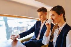 Een modieus paar drinkt ochtendkoffie bij de koffie, de jonge zakenlieden en freelancers royalty-vrije stock fotografie