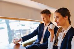 Een modieus paar drinkt ochtendkoffie bij de koffie, de jonge zakenlieden en freelancers stock afbeelding