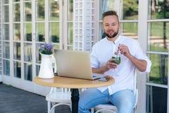 Een modieuze aantrekkelijke mens gekleed in een wit overhemd en jeans, heeft een Europese verschijning, een kort kapsel en een ba royalty-vrije stock foto