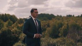 Een modieuze jonge mens bevindt zich in de wind tegen de achtergrond van een mooi bos en kijkt ernstig in de afstand stock videobeelden