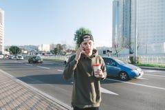 Een modieuze jonge student die rond de stad met een kop wandelen en op de telefoon spreken Tegen de weg met auto's Levensstijl en Stock Afbeeldingen