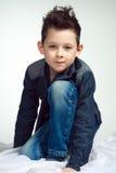 Een modieuze kleine jongen is zo aantrekkelijk Een jong geitje zit op zijn k Royalty-vrije Stock Afbeelding