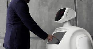 Een modieuze mens communiceert met een robot, drukt een plastic mechanisch wapen aan de robot, handdruk Cybernetisch systeem stock footage