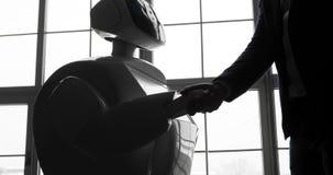 Een modieuze mens communiceert met een robot, drukt een plastic mechanisch wapen aan de robot, handdruk Cybernetisch systeem stock videobeelden