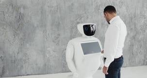 Een modieuze mens communiceert met een robot, drukt een plastic mechanisch wapen aan de robot, handdruk Cybernetisch systeem stock video