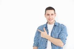 Een modieuze ongeschoren mens in een overhemd richt aan een exemplaar van de ruimte op een witte muur, aangezien aardig iets toon royalty-vrije stock afbeeldingen