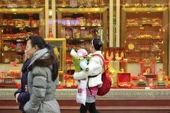 Een moeder die een kind houdt om door een gouden winkel over te gaan Stock Afbeeldingen