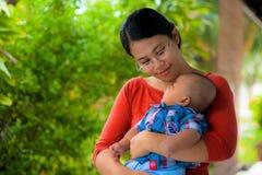 Een moeder die haar baby met liefde houdt. Royalty-vrije Stock Afbeelding