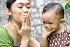Een moeder die haar babymeisje onderwijst kust vaarwel Royalty-vrije Stock Afbeelding