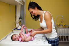 Een moeder die haar babynappy veranderen. Royalty-vrije Stock Foto