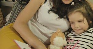 Een moeder die haar dochter een boek lezen vóór bed stock videobeelden