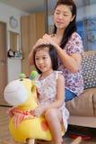 Een moeder die haar dochter` s haar kammen stock foto's