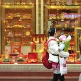 Een moeder die in het venster van een gouden winkel kijkt Stock Afbeelding