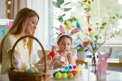 Een moeder en een dochter die Pasen vieren, schilderend eieren met borstel stock foto