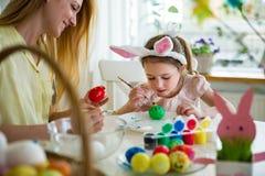 Een moeder en een dochter die Pasen vieren, schilderend eieren met borstel royalty-vrije stock foto's
