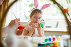 Een moeder en een dochter die Pasen vieren, schilderend eieren met borstel royalty-vrije stock fotografie
