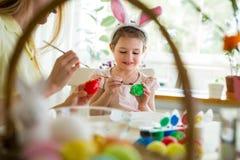 Een moeder en een dochter die Pasen vieren, schilderend eieren met borstel royalty-vrije stock foto