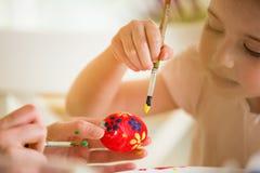 Een moeder en een dochter die Pasen vieren, schilderend eieren met borstel stock afbeelding