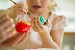 Een moeder en een dochter die Pasen vieren, schilderend eieren met borstel stock foto's