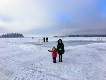 Een moeder en een dochter die van de winter genieten door op het bevroren meer van Astotin-Meer te lopen stock foto's