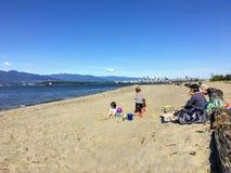 Een moeder en drie kinderen bij strand het spelen in het zand op een mooie zonnige dag langs Spaanse Banken royalty-vrije stock foto