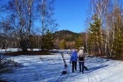 Een moeder en een dochter die in de de wintersneeuw lopen Royalty-vrije Stock Foto