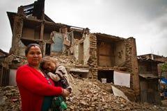Een moeder en een kind buiten een aardbeving ruïneerden huis in Bhaktap Stock Foto