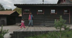 Een moeder en haar kind lopen voorbij een buitenhuis stock video