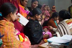 Een moeder en een kind verzamelden zich in de kliniek voor de armen stock foto