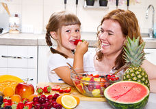 Een moeder geeft aan het meisje een fruitsalade in de keuken Royalty-vrije Stock Foto's