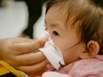 Een moederhand die haar dochter lopende neus schoonmaken royalty-vrije stock afbeelding