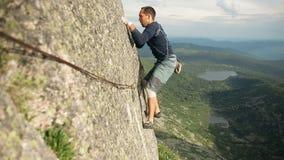 Een moedige jonge mens beklimt alleen een hoge rots zonder verzekering