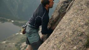 Een moedige jonge mens beklimt een hoge rots zonder verzekering stock videobeelden
