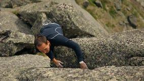 Een moedige mens beklimt een rots stock videobeelden