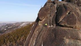 Een moedige mens beklimt tot de bovenkant van de klip stock footage