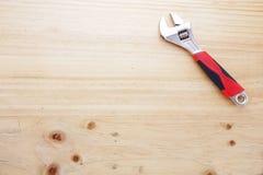 Een moersleutel op een houten lijst stock afbeelding
