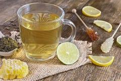 Een mok thee met citroenplakken en suiker op een stok stock foto's