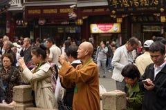 Een monnik kleedde zich in oranje robes onder menigte van mensen Stock Fotografie