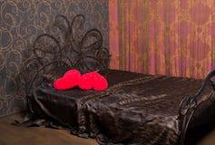 Een mooi bed met rode hoofdkussens Stock Afbeeldingen
