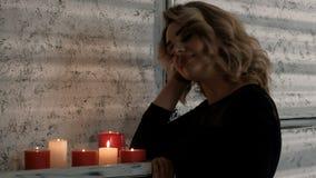 Een mooi blond meisje in een zwarte kleding nadert de plank met het branden van kaarsen Het wachten op een avondvergadering of a stock video