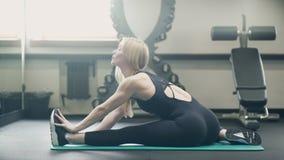 Een mooi blonde in een sportclub rekt haar benen en billen uit stock video
