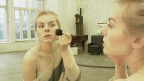 Een mooi blonde zet op een make-up met een grote borstel op haar wangen Een jonge vrouw gaat op zich een datum en het kleden stock video